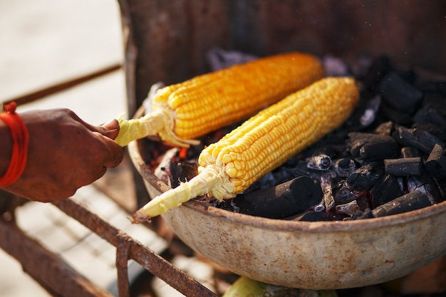 グリルのトウモロコシの穂軸。トウモロコシと手で画像を閉じます。アジア、インド、中国の屋台料理。 goaサンセットのフードビーチ Premium写真