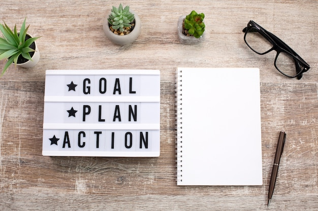 Goal, plan, action text on light box and notebook Premium Photo