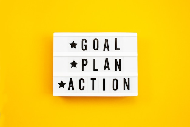 Goal, plan, action text on light box on yellow background. Premium Photo