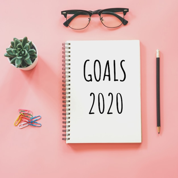 Goals 2020 and notepad and stationery on pink pastel Premium Photo