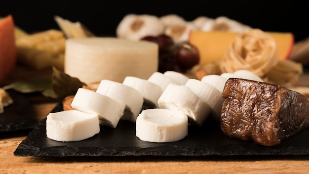 Goat cheese and brunost cheese on black rock slate Free Photo