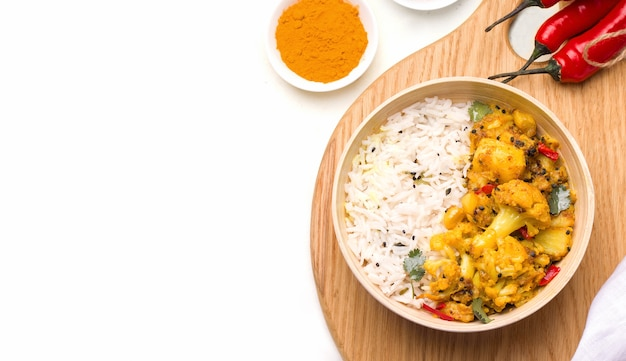 Gobi aloo indian vegetarian dish of vegetables and potatoes in a bowl on a wooden board on white Premium Photo
