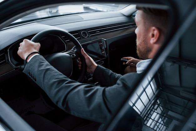 Andando avanti. coppie riuscite adorabili che provano la nuova automobile nel salone dell'automobile Foto Gratuite
