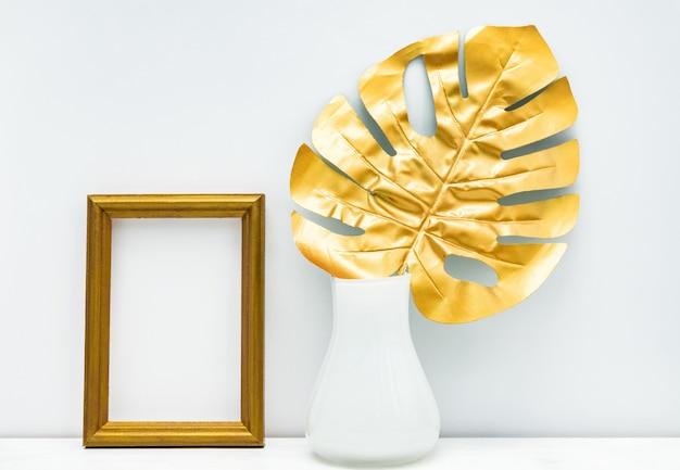 金と白のインテリアモックアップデザイン。空のフォトフレームとモンステラリーフ白い壁の背景に白い花瓶。 Premium写真