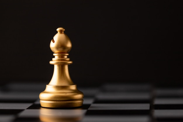 Gold bishop on the chess board Premium Photo