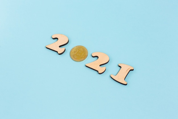 Gold bitcoin and wooden numbers 2021 lies on a blue surface Premium Photo