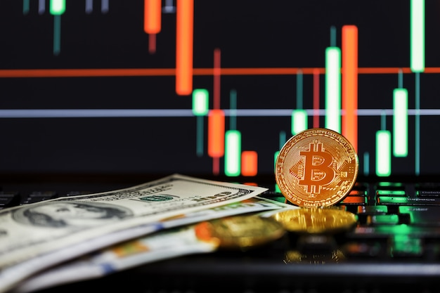 Gold bitcoins on the background of business charts close-up and 100 dollar bills. Premium Photo