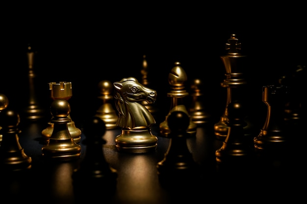 Gold chess on black background , focus on knight Premium Photo