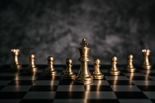 Золотые шахматы на шахматной настольной игре для концепции лидерства в метафоре бизнеса Бесплатные Фотографии