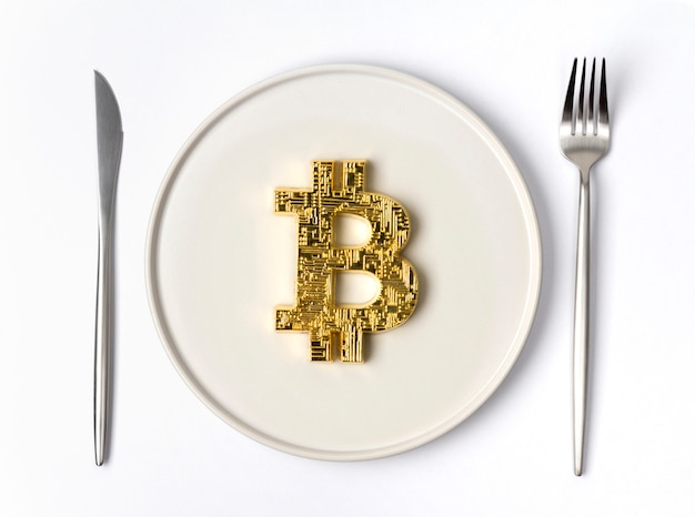 Gold coin bitcoin served on white empty plate Premium Photo