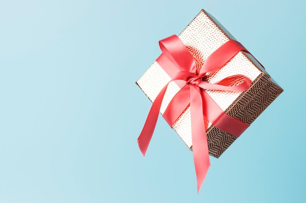 Gold color gift box with pink ribbon Premium Photo