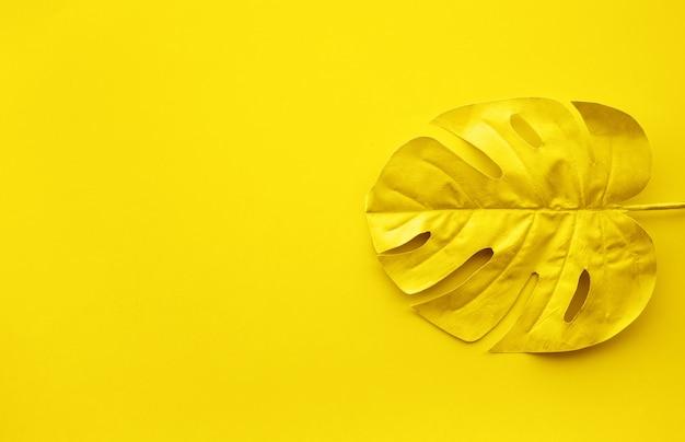コピースペースの背景を持つ熱帯の葉のゴールドカラー Premium写真