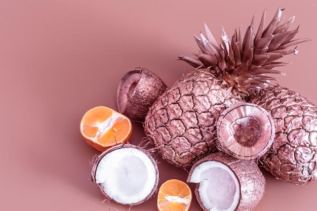 色付きの背景に金色の果物。トロピカルフラットレイ。食品のコンセプト。 無料写真