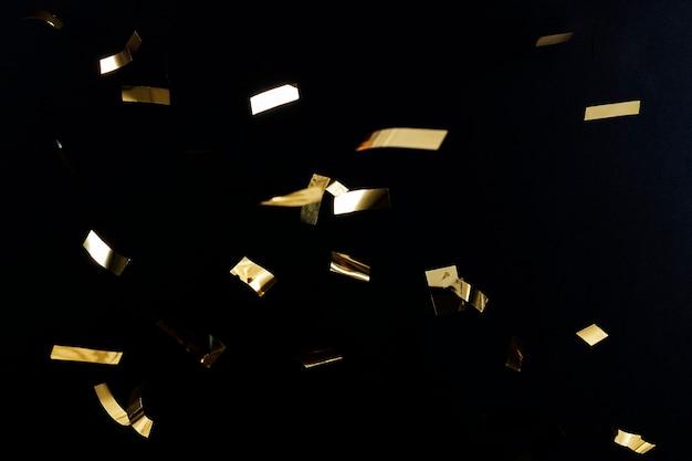 黒の壁紙に金の紙吹雪パターン 無料写真