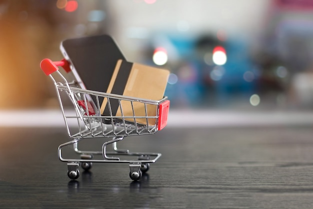 Gold credit card and smartphone in small shopping cart conceptual of internet shopping Premium Photo