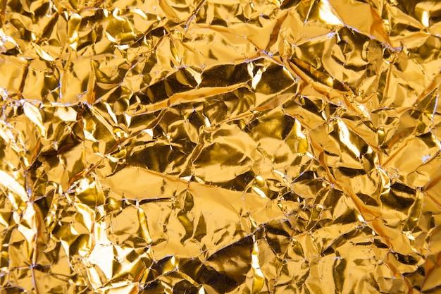 Gold crumpled foil paper texture background. Premium Photo