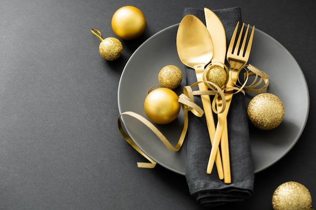 Gold cutlery served on plate for christmas dinner Premium Photo