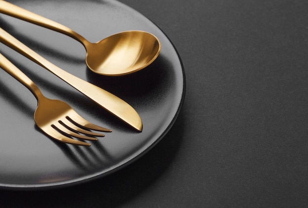 Gold cutlery set on black background Free Photo
