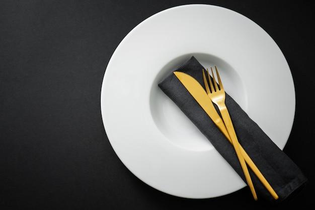 Gold cutlery set on black Premium Photo