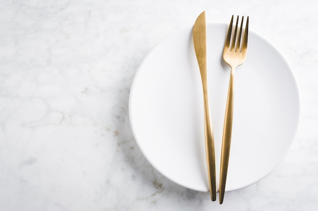Gold cutlery set on marble Premium Photo