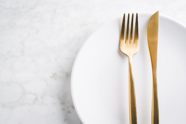 Gold cutlery set on marble Free Photo