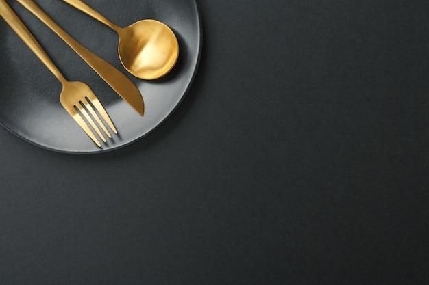 Набор золотых столовых приборов на черном фоне Бесплатные Фотографии