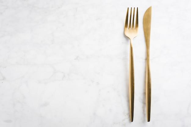 Набор золотых столовых приборов на мраморе Бесплатные Фотографии