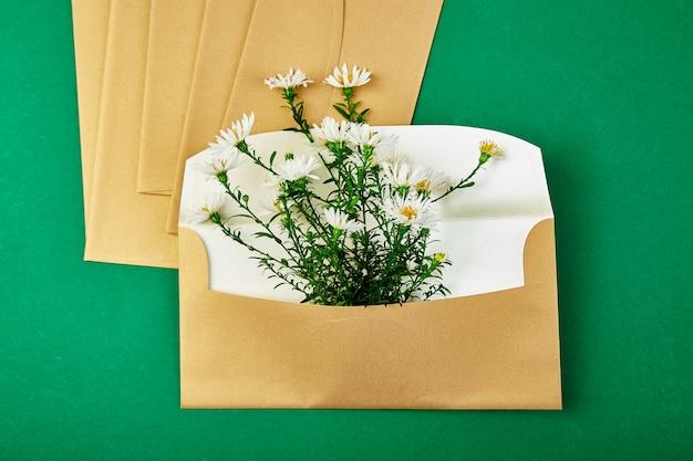 Gold envelope with a spring flower arrangement Premium Photo