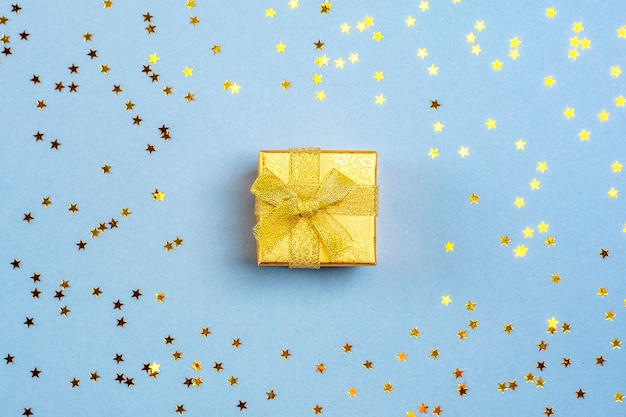 Gold gift box and sparkles in the shape of stars on a blue background flat lay Premium Photo
