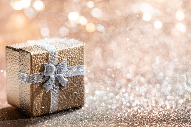 Gold gift box with magical light on glitter bokeh  for christmas holidays. Premium Photo