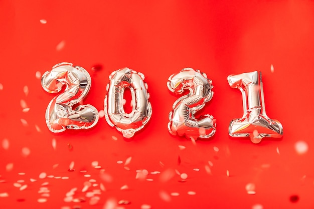 Gold helium balloons forming happy new year 2021 congratulation, christmas celebration decoration isolated on red background Premium Photo