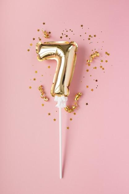 Золотая надувная цифра 7 на палочке золотого конфетти на розовом фоне. понятие праздника, дня рождения, юбилея. Premium Фотографии