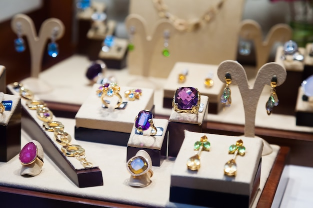 Gold jewelry with gems at showcase Free Photo