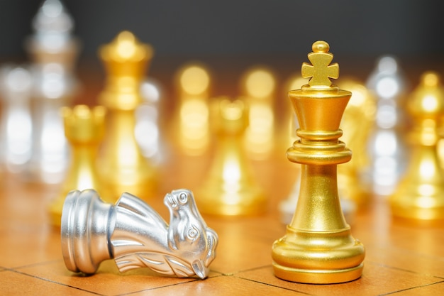 Gold king chess piece and horse chess pieces stand on wood chessboard ,concept of leadership game of strategy Premium Photo