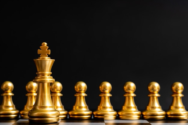 Gold king chess piece stand in front of pawn on black