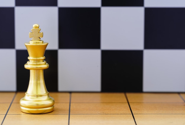 Gold king chess piece stand on wood chessboard ,concept of leadership game of strategy Premium Photo