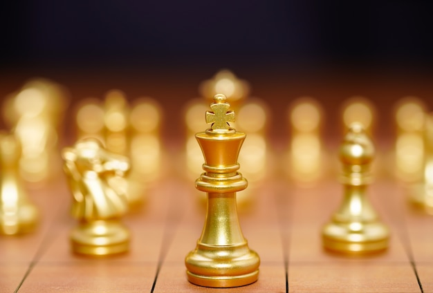 Gold king chess piece and various chess pieces stand on wood chessboard ,concept of leadership game of strategy Premium Photo