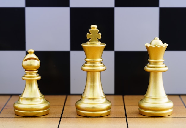 Gold king chess piece and various chess pieces stand on wood chessboard tegy Premium Photo