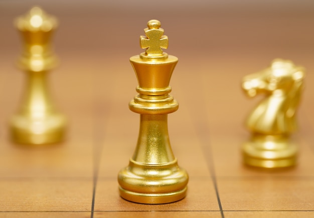 Gold king chess piece and various chess pieces stand on wood chessboard Premium Photo