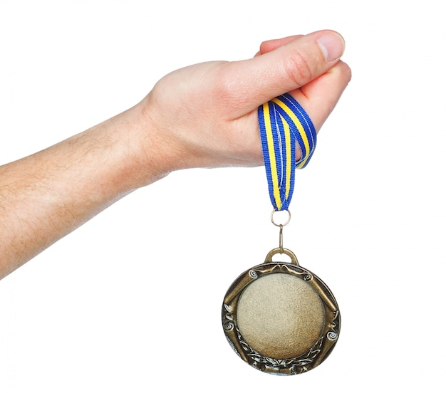 Gold medal winner in the hand. on a white wall. Premium Photo