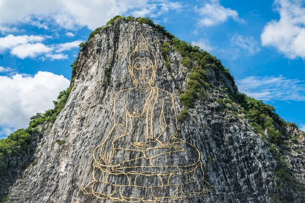 Gold painting of buddha statue on cliff at cheechan mountain Premium Photo