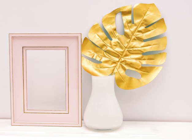 Gold, pink and white interior mockup design. empty photoframe and monstera leaf in white vase on white wall background. trendy luxury design. Premium Photo