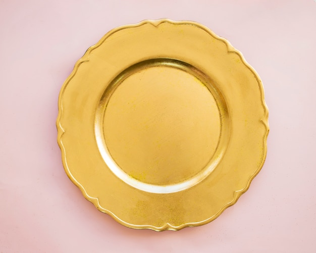 Gold plate on pink table Free Photo
