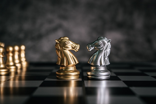 Gold and silver chess on chess board game for business metaphor leadership concept Free Photo