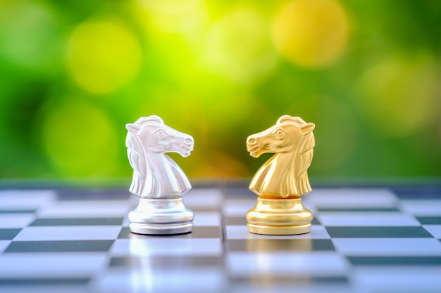 Gold and silver chess knight piece on chessboard. Premium Photo