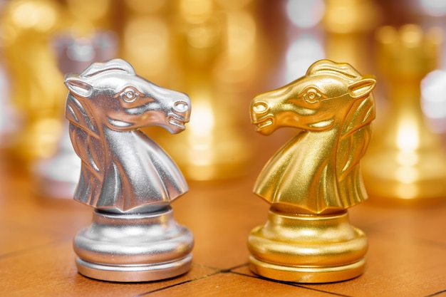 Gold and siver horse of the chess in the game on chessboard Premium Photo