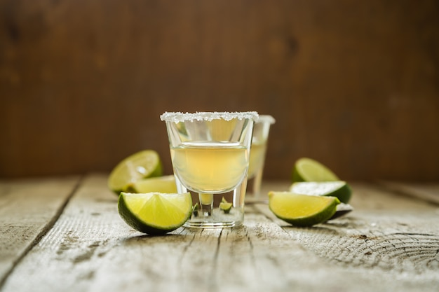 Gold tequila shots on rustic wood Premium Photo