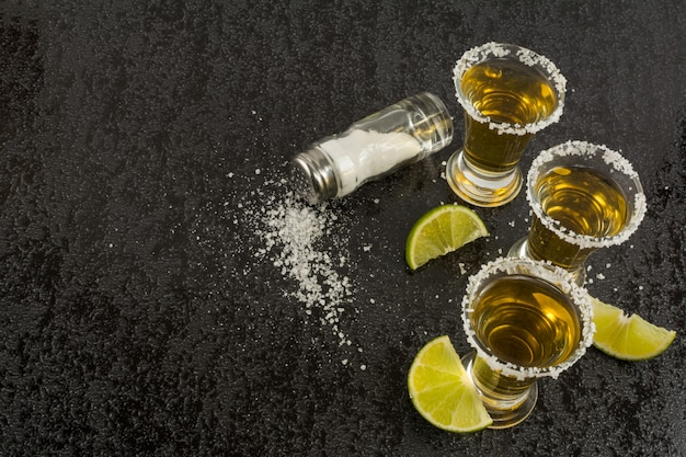 Gold tequila with lime on black background, top view Premium Photo
