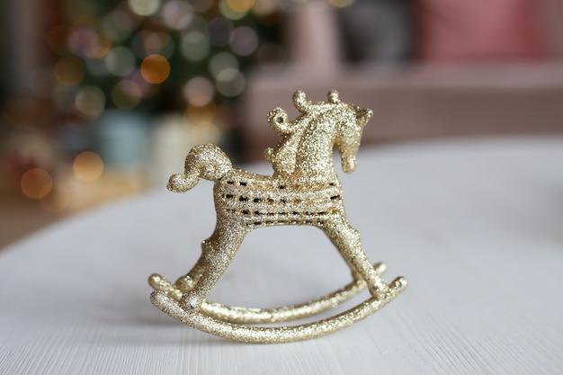 木のボケと花輪を背景にテーブルの上に立っている金のおもちゃの装飾馬 Premium写真