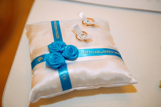 リボンと花で飾られた白いクッションの金の結婚指輪のクローズアップ。結婚式のテーマ、新婚夫婦のためのアクセサリー。 Premium写真